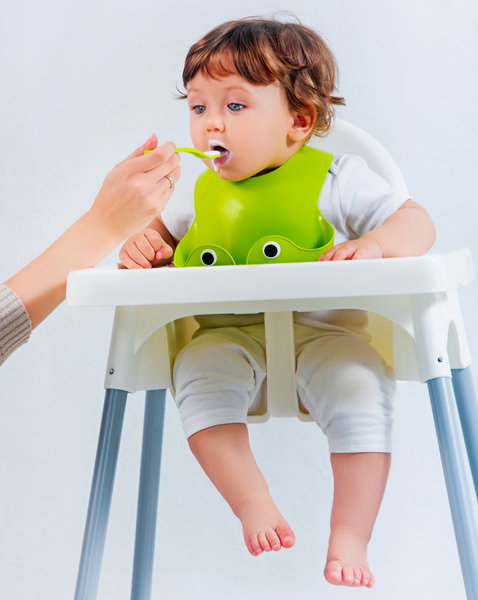 Toddler eating puree with a spoon