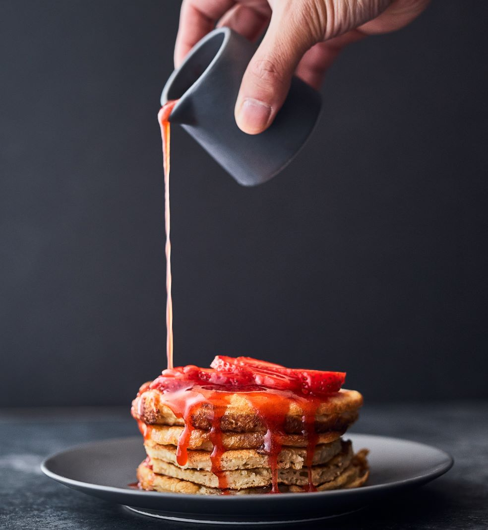 man pouring strawberry puree on pancakes